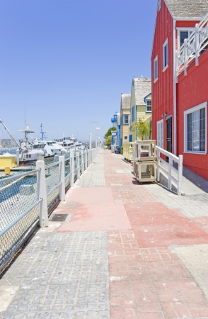 Fisherman s Village stone walkway, Marina Del Rey  Commercial shopping resort and tourist attraction  Weathered brick paved path bordered by colorful wooden buildings and boats docked in the marina  Clear blue sky  Vertical photo, perspective view  Stock Photo - 20465920