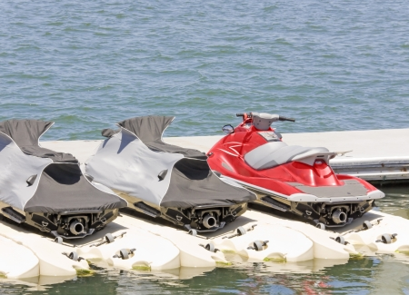 Personal water craft, jet skis at the dock   Bright red jet ski next to 2 covered jet skis docked at the marina in calm blue water  Rear view showing the jet nozzle  Horizontal photo  Stock Photo