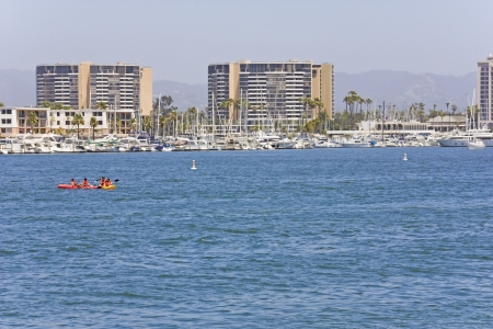 Marina Del Rey harbor near Los Angeles   Southern California lifestyle depicted by busy harbor development with kayaking, boating  Docks for yachts, large buildings, hills in the background   photo