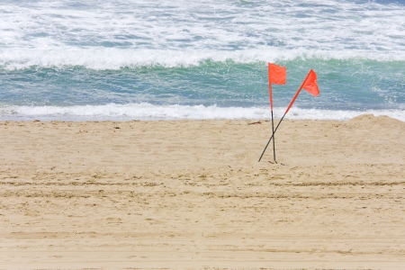 foam safe: Swimming safety, two beach flags criss crossed in the sand  2 red lifeguard flags show where it is safe to swim at the beach  Blue ocean with surf, white foam rolling in the background  Horizontal, room for text, copyspace