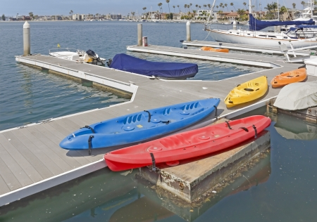 Colorful kayaks on the waterfront  Four bright red, blue, yellow, orange kayaks on a wooden dock near the boat slips at Naples marina, Southern California  Horizontal scene, anchored motorboat, sailboats in background  photo