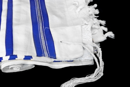 Tallit, Jewish prayer shawl  White wool cloth garment with knots and fringes worn by Jewish men during prayer services  Blue stripes indicate Sephardic style and custom  Isolated on a black background  photo