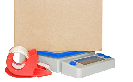 shipment parcel: Ready for shipment  Weighing a large brown cardboard box on a blue and grey digital postal scale  Bright red mailing tape dispenser in foreground  Horizontal photo, space for text  Isolated on a white background  Stock Photo