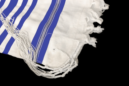 jewish symbols: Tallit, Jewish prayer shawl for religious observance  White wool cloth garment with knots and fringes worn by Jewish men during prayer services  Blue stripes indicate Sephardic style and custom  Isolated on a black background