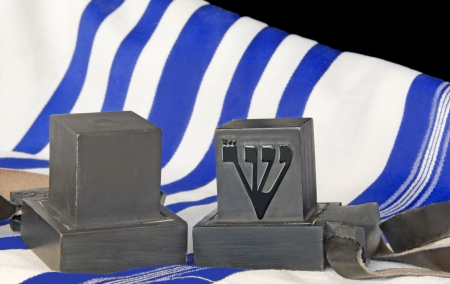 Tallit and tefillin  Pair of black boxes with leather straps  Portions of the Torah written on parchment inside  Worn by Jewish men during prayer  White wool cloth garment with blue stripes indicate Sephardic style and custom   photo