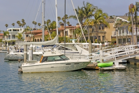 Luxury boats anchored at the dock, Naples marina, Southern California, near Los Angeles  Horizontal scene, hazy blue sky  Palm trees, residential buildings sit near the water photo
