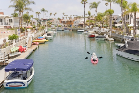 townhomes: Rowing in the blue water  Colorful scenic small boats, kayaks  Expensive homes, townhomes, apartments, condos at water Stock Photo