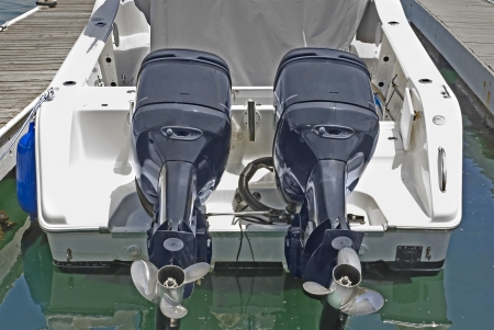 pleasure boat: Dual outboard motors   Rear view of white motorboat, 2 identical engines showing propellers  Reflection of boat in water  Horizontal scene
