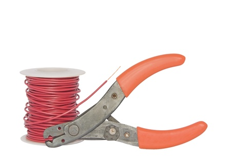 Wire cutter, insulated copper wire wound on a plastic spool  Metallic wire stripper with orange handles and numbered gauge to measure wire diameter  End of wire is stripped showing bare copper  Isolated on a white background  photo