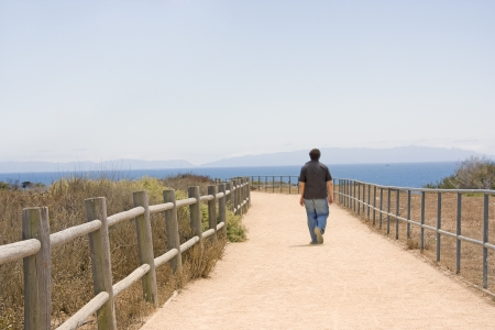 other side of: Boy walking alone on cliff path   Solitary teen walking away on a rural path by the ocean  Wood split rail fence on one side of trail, metal railing on other side  Blue sky, water  Catalina island in the background