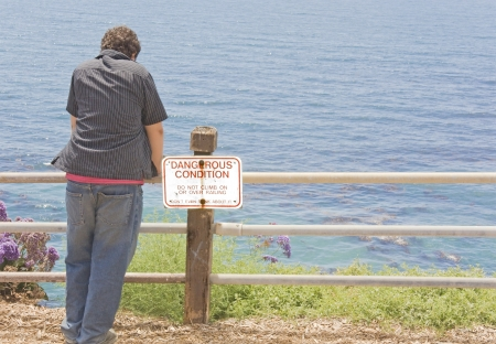 Dangerous cliff edge at the ocean   A teenager leaning on a safety fence with warning sign, thinking about climbing over the metal railing on to the steep cliff edge  photo