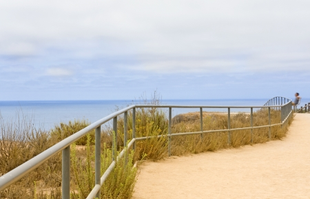 Ocean hillside on overcast day   A metal rail safety fence twists and turns along a cliff edge hiking path  Person sitting on a bench at far right looking out over the blue ocean and cloudy sky  photo