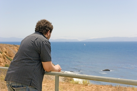 overlook: Young man leaning on metal railing of a safety fence on a cliff edge overlooking the ocean   Back view of person wearing jeans, black striped shirt  Blue water, sky, rocky hillside, Catalina island in the background
