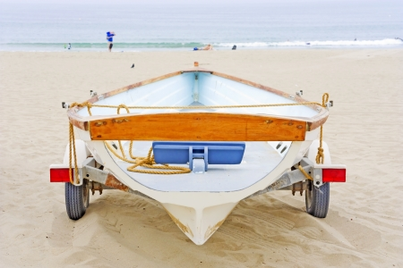 small boat: Small boat on trailer in the sand   Rear view of wood and fiberglass v-hull shaped boat parked on beach  Boat tied to trailer with wheels and red taillights  People, blue water, waves in background  Horizontal scene  Stock Photo