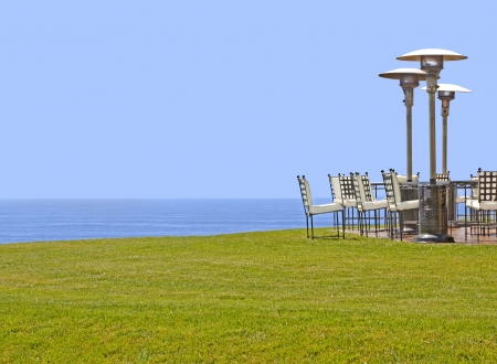 Outdoor furniture on a grassy cliff overlooking the ocean   Chairs with metal frames, white cloth seats, tall standing patio heater lamps on hard flooring  Scenic view of calm ocean water and blue sky background  Horizontal view  Stock Photo