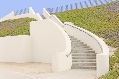 ground cover: Outdoor stone stairs   Concrete steps curving down a steep hillside  Green succulent ground cover on hill  Asphalt, sand at bottom of stairway  Elegant, winding architecture  Metal handrail  Rail fence, blue sky background  Horizontal scene