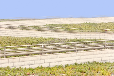 iceplant: Changing direction   Outdoor pedestrian walking ramp zigzags down a steep hillside  White brick walls  Metal handrail  Blue sky background  Small child walking at far right  Green succulent ice plant ground cover on hill  Horizontal photo