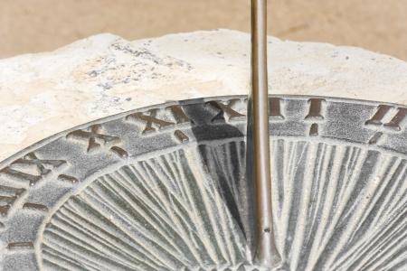 reloj de sol: Sundial cerca Vista parcial de gris y marrón de metal reloj de sol montado en White Rock números romanos marca las horas en la sombra de la cara muestra el tiempo a ser un poco después del 11 de 00 de la mañana
