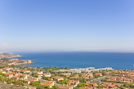 Ocean view luxury homes   Aerial view, Southern California coastline, cluster of trees and red tile rooftops overlooking the calm blue water  Horizontal, wide angle panoramic view  Room for text, copyspace  photo