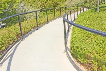 going down: Liquidaci�n sendero del parque sendero pavimentado que va abajo entre exuberante follaje verde y flores plantas metal barandilla en cada Horizontal Vista en perspectiva lateral de fotos