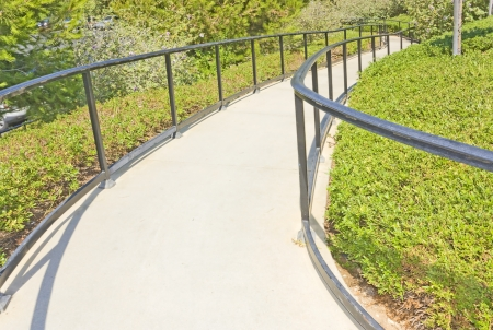 Winding park path   Paved footpath going down between lush green foliage and flower plants  Metal railing on each side  Horizontal photo  Perspective view  Stock Photo - 21802247