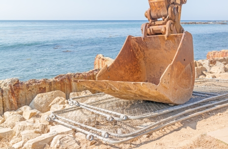 Excavator shovel parked at ocean work site   Close up of heavy construction equipment front bucket resting on dismantled wire fence panels on rocky surface  Remains of low concrete wall, blue ocean and sky in background  Horizontal photo Stock Photo - 22613093