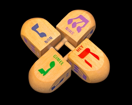 hebrew letters: Jewish holiday colorful Chanukah dreidels    Group of large wood dreidels isolated on a black background  Bright green, blue, red, purple color Hebrew letters gimmel, nun, hey, shin   Stock Photo