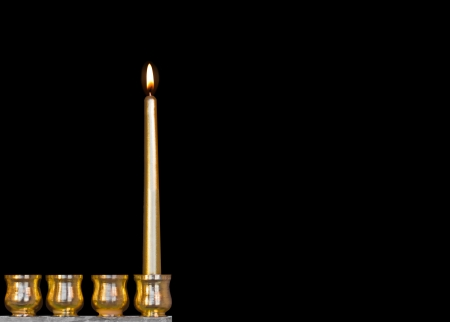 jewish holiday: One Jewish holiday Chanukah candle   Bright, shiny yellow candle glowing for the first night of Chanukah  Gold color menorah cups  Room for text, copy space  Isolated on a black background  Horizontal photo