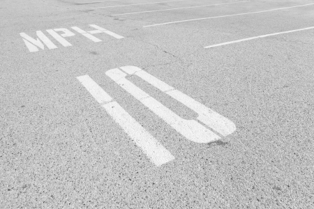 Urban parking lot speed limit road markings   Grey textured asphalt, empty parking spaces, white dividing lines  10 mph speed limit in painted white letters on ground  Close up, perspective view  Horizontal, black and white photo  photo