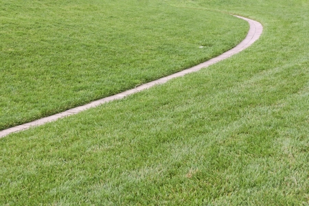 Narrow brick paved path curving through grassy field   Peaceful empty walkway, sharp curve through trimmed green grass, vanishing in the distance  Horizontal, perspective view  photo