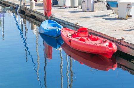 fiberglass: Kayaks rojos y azules brillantes atracados en muelle kayaks vacíos vinculados con grapas en el muelle de madera Reflexiones en el azul escena Horizontal aguas tranquilas