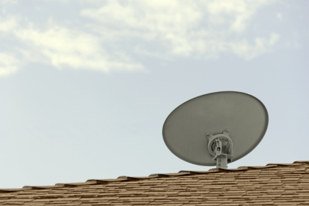tilted view: Home satellite dish antenna on roof, rear view, sky, clouds   Back of outdoor home antenna facing the sky, mounted on brown roof shingles  Blue cyan, cloudy, background  Horizontal view  Copyspace, room for text  Stock Photo
