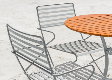 seating furniture: Casual outdoor patio furniture, wood plank circular table and metal chairs on stone floor   Bright orange table  Two aluminum tube frame chairs