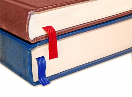 closed ribbon: 2 closed stacked books with bright red and blue ribbon bookmarks   Close up edge of two worn hardcover books, leather texture, isolated on a white background  Slight drop shadow  Angled, perspective view  Horizontal photo