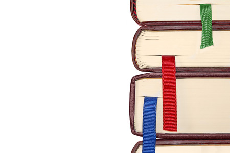 closed ribbon: Closed stacked books with bright blue, red, and green ribbon bookmarks   Close up edge of brown hardcover books, isolated on a white background  Horizontal photo  Room for text, copyspace