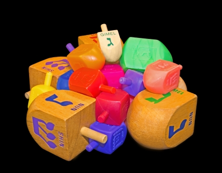 Group of colorful Chanukah dreidels   Pile of wood and plastic Jewish holiday dreidels isolated on a black background  Mulicolored Hebrew letters gimmel, nun, hey, shin   photo