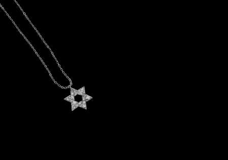 Jewish Star of David necklace isolated on a black background    Shiny silver color, textured six point star pendant on a link chain  Horizontal photo  Room for text, copyspace  photo