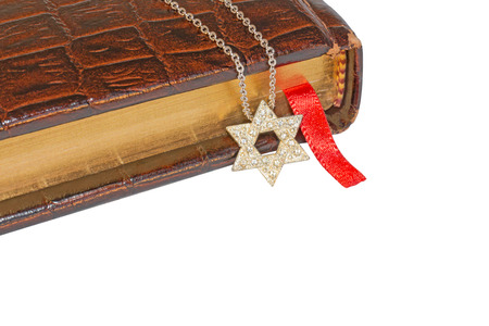 Jewish Star of David necklace, old brown leather prayer book, red ribbon bookmark   Shiny silver, textured six point star pendant on link chain hanging over closed hardcover book  Horizontal photo  Room for text, copyspace  photo