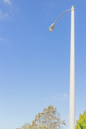 cement pole: One tall city streetlight during the day   View from below  Light bulb in metal enclosure mounted on cement pole  Treetops at bottom of photo  Wispy white clouds, blue sky background  Vertical