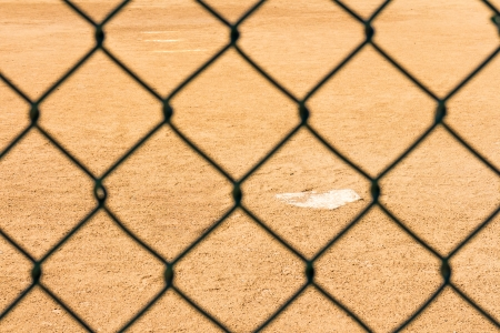 homeplate: Home plate viewed from behind the backstop   Selective focus on white home plate and sandy infield  Blurred chain link fence  Horizontal photo