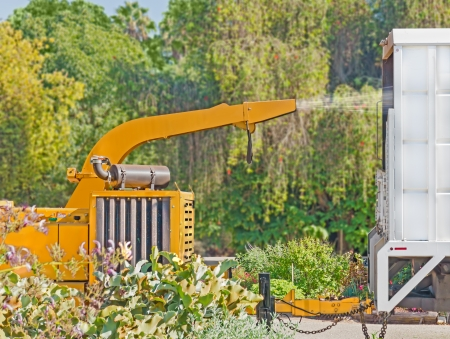 shreds: Industrial yellow wood chipper machine, truck profile   Heavy, noisy machinery chops, shreds, and sprays wood chippings into back of a white truck  Chipper attached to truck with a trailer hitch  Trees in background