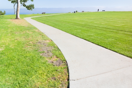 paved: Long, curving paved path through a suburban park grassy field   Green grass on both sides of lined pavement  Tree, benches, bushes, jogger in background  Low overcast cloud cover in the distance  Horizontal photo, wide angle perspective view
