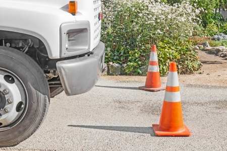 Two bright orange traffic cones in front of large truck   Side view  White truck with grey bumper parked on pavement  Strong shadow of cones pointing toward truck  Greenery, flower bushes in background     photo