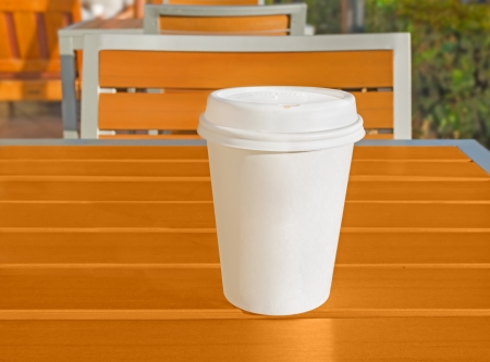 Wake up with coffee in early morning light   Paper coffee cup with lid on wood table at outdoor cafe  Tables, chairs with metal frames  Blurred background, person at upper left of photo  photo