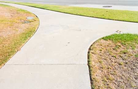 forked road: Sidewalk and grass near street   Suburban scene  Winding, forked road  Concrete pavement  Dry green and brown grass  Nice for drought or decision making concept
