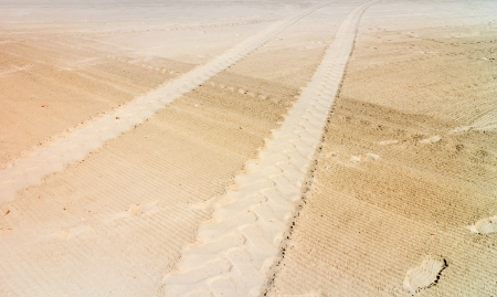 flat tyre: Tracks and lines in the sand   Perspective view of large heavy vehicle tire tread imprint contrasting with small human footprint  Lines crisscross over the sandy surface  Horizontal scene   Stock Photo