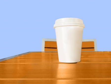 Wake up with coffee   White paper coffee cup with lid on wooden table  Table, chair with metal frame  Blue sky background   photo