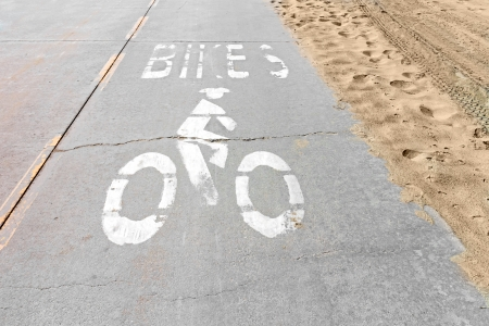 Old, worn bike path at the beach   Well used cycle route by the sand  Stained, cracked, pitted pavement with painted bicycle symbol  Horizontal photo  photo