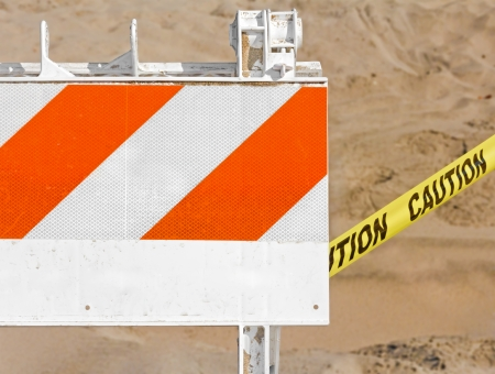 impede: Construction barricade in the sand   Bright orange stripes and the word  caution  on yellow ribbon  Sandy, blurred background  Horizontal photo