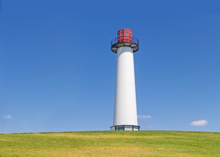 Long Beach California harbor lighthouse   Also known as Rainbow Point Lighthouse  View from below on grassy hill  Blue sky, small clouds  No water, no people in scene  Color of building white, black, and red  Room for text, copyspace  Horizontal photo  photo